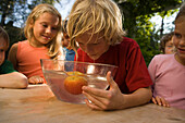 Boy with wet hair bending over a dish with water and an apple, children's birthday party