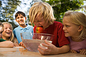 Boy with wet hair holding an apple in his mouth, dish wath water in front of him, children's birthday party