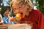 Boy with wet hair holding an apple in his mouth, dish wath water in front of him, children's birthday