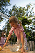 Wet girl bending over a dish with water and an apple, children's birthday party