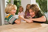 Two boys arm wrestling, girls standing in background, children's birthday party