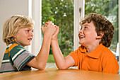 Two boys arm wrestling, children's birthday party