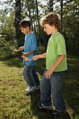Two boys playing egg-and-spoon race, children's birthday party