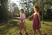 Two girls playing egg-and-spoon race, children's birthday party