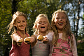 Three girls playing egg-and-spoon race, children's birthday party