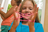 Girl playing cat's cradle, children's birthday party