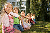 Children crouching on grass and making grimaces, children's birthday party