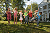 Children holding hands and jumping, children's birthday party