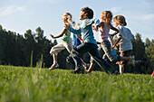 Children running across a field, children's birthday party