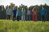 Children standing side by side on grass, children's birthday party