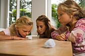 Three girls playing Blowing Cotton Wool, children's birthday party