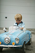 Young boy sitting in toy car
