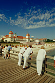 Vacationers standing on beach bridge and looking over beach and spa hotel, Binz, Ruegen, Mecklenburg-Western Pomerania, Germany