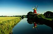 Mirroring of windmill on water surface, Greetsiel, East Friesland, Lower Saxony, Germany