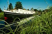 Ship on canal, reflection on water surface, Westrhauderfehn, Rhauderfehn, East Friesland, Lower Saxony, Germany