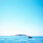 Small fishing boat on Adriatic Sea, island in background, Dalmatia, Croatia