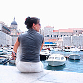 Female tourist sitting at harbour near city wall, Dubrovnik, Dalmatia, Croatia