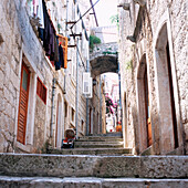 View inside an alley wiht old stone houses and clotheslines at facade, Korcula, Dalmatia, Croatia