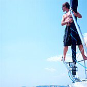 Man standing on sailboat's railing an lookin at view, Adriatic Sea, Dalmatia, Croatia