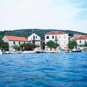View over Adriatic Sea to old stone houses and small boats, Stari Grad, Hvar, Dalmatia, Croatia