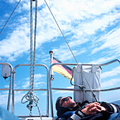 Man resting on deck of a sailboat, Bay of Kiel between Germany and Denmark