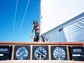 Man on sailboat, fixing a sail, control panel in foreground, Bay of Kiel between Germany and Denmark