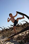 Boy playing on a rosty anchor at beach, Ilha de Tavira, Tavira, Algarve, Portugal