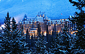 A big house a building in the winter in the forest. Evening, Banff Fairmont Springs Hotel, Rocky Mountains, Alberta, Canada, North Amerika