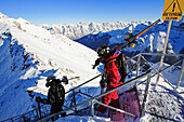 Two young men carry their skis down  on some stairs to the extrem rund Delirium Dive at the ski resort Banff Sunshine, Alberta, Rocky Mountains, Canada, North Amerika.