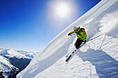 Ein junger Mann, ein Skifahrer fährt einen Steilhang hinunter, Abfahrt vom Berg Popova Kapa, Bulgarien, Rila Gebirge. Europa