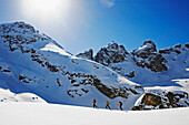 A group of skitourists climb with skis and skins to the top of the Popova Kapa in the Rila Mountains, Bulgaria