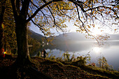 A couple walking along the shore of lake Kochelsee in Autumn, Bavaria, Germany
