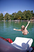 Child sliding into the water from a boat, Walchstadt, Wörthsee, Bavaria, Germany