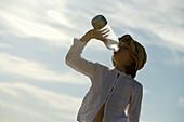 Girl drinking a bottle of water, Travemuende Bay, Schleswig-Holstein, Germany