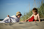 Girl and boy playing at sandy beach of Baltic Sea, Travemuende Bay, Schleswig-Holstein, Germany