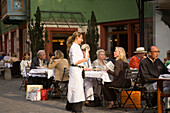 Waiter attending a guest in a pavement cafe, Augustinergasse, Zurich, Canton Zurich, Switzerland