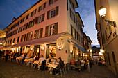 Guests sitting in a pavement cafe at a corner near Hirschplatz in the evening, Niederdorfstrasse, Zurich, Canton Zurich, Switzerland