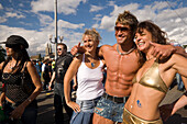 Muscular shirtless man with arms around two young women smiling at camera, Street Parade (the most attended technoparade in Europe) near Quai Bridge, Zurich, Canton Zurich, Switzerland