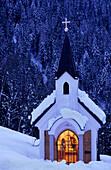 Snow covered illuminated chapell in evening mood, Alpendorf, St. Johann im Pongau, Salzburg, Austria