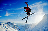 A young skier, a freerider jumping over a snow cornice with crossed skis at the Parsenn Ski area, Davos, Klosters, Grisons, Graubuenden, Switzerland, Europe, Alps