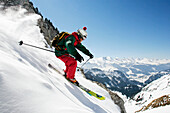 A young skier, a freerider skis down a steep slope in powder snow at the Saentis mountain, with the Churfirsten mountains in the background, Appenzell, St. Gallen, Toggenburg, East Switzerland, Switzerland, Alps
