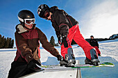 A young snowboard instructor teaches a child a trick on a frame box at the funpark snowland near Wildhaus, Toggenburg, St. Gallen, East Switzerland, Switzerland, Europe, Alps