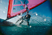 Windsurfer performing a turn, hand in water, Windsurfing, Sport