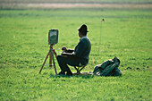 A man painting scenery near Breitbrunn, Lake Chiemsee, Upper Bavaria, Bavaria, Germany, Europe