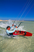 Man kiteboarding at great speed, gripping line with two hands