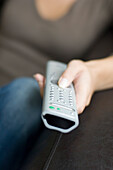Young woman using remote control, close-up