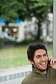 Young man at bus stop phoning with a mobile phone