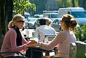 Two young women sitting in a pavement cafe, Munich, Bavaria, Germany