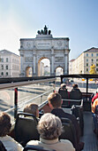 Sightseeing tour bus passing Siegestor (Victory Gate), Munich, Bavaria, Germany
