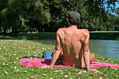 Naked young man sunbathing near Eisbach, English Garden, Schwabing, Munich, Bavaria, Germany